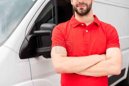 Photo for Cropped shot of delivery man in red uniform with arms crossed standing at van - Royalty Free Image
