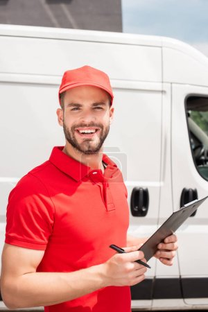 cheerful delivery man in red uniform with notepad looking at camera