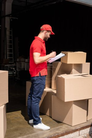 side view of delivery man in uniform checking notes in notepad