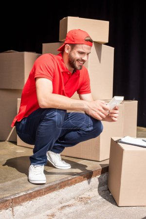 young smiling delivery man making calculations on calculator near cardboard boxes