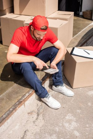 high angle view of young delivery man making calculations on calculator near cardboard boxes
