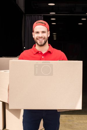 Photo for Portrait of smiling delivery man in uniform holding cardboard box - Royalty Free Image