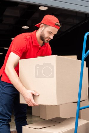 side view of delivery man putting cardboard boxes on delivery cart