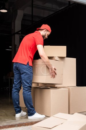 young delivery man in red uniform with cardboard boxes