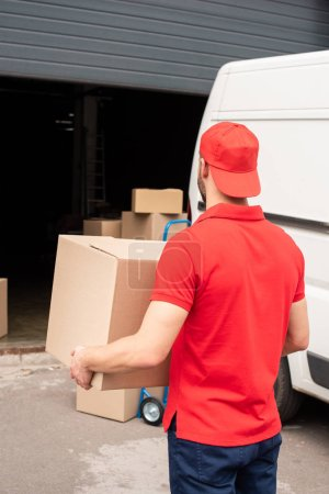 back view of delivery man in red uniform carrying cargo
