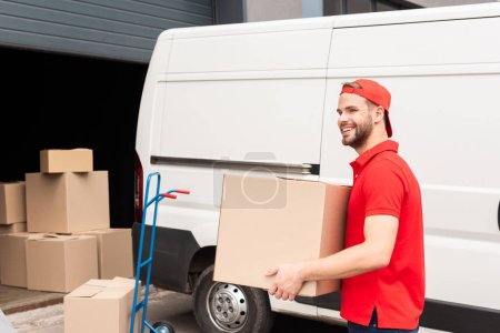Photo for Smiling delivery man in uniform with cardboard box standing near white van in street - Royalty Free Image