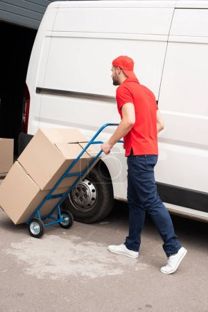 side view of delivery man with cardboard boxes on delivery cart