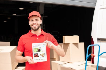 portrait of smiling delivery man showing tablet with ebay website on screen in hands with cargo behind