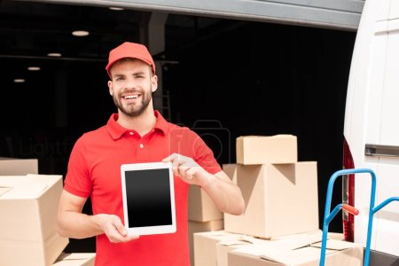 portrait of smiling delivery man showing tablet with blank screen in hands with cargo behind