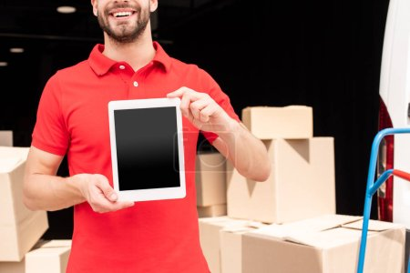 cropped shot of smiling delivery man showing tablet with blank screen in hands with cargo behind