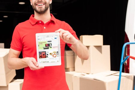 cropped shot of smiling delivery man showing tablet with ebay website on screen in hands with cargo behind