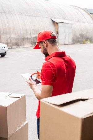 side view of delivery man in red uniform using digital tablet