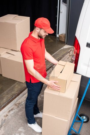 Photo for High angle view of young delivery man discharging cardboard boxes from van - Royalty Free Image