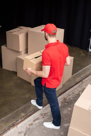 high angel view of young delivery man in red uniform discharging cargo