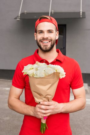 portrait of cheerful delivery man holding bouquet of roses on street