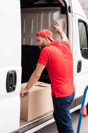 young delivery man in red uniform standing near van with cargo