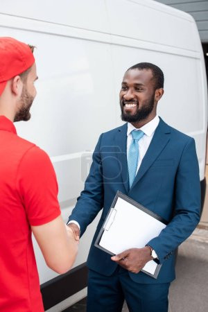 smiling delivery man and african american businessman shaking hands