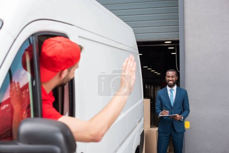 delivery man in van waving to smiling african american businessman with notepad