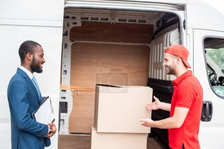 caucasian delivery man showing cargo to african american client