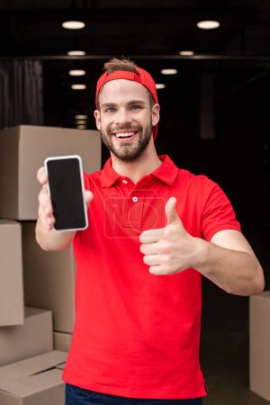 portrait of cheerful delivery man with smartphone showing thumb up
