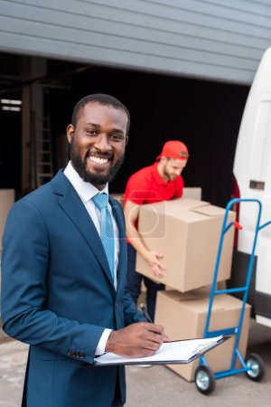 selective focus of multicultural businessman and delivery man