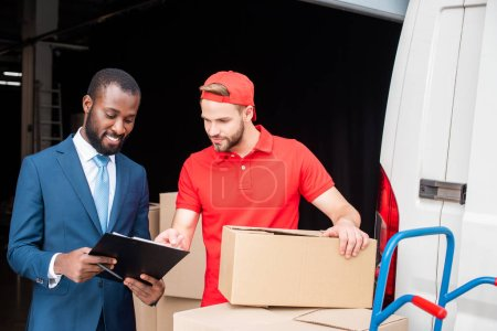 portrait of multicultural businessman and delivery man discussing order