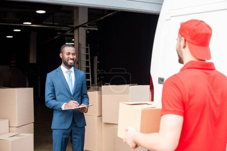 selective focus of multicultural businessman and delivery man with cargo
