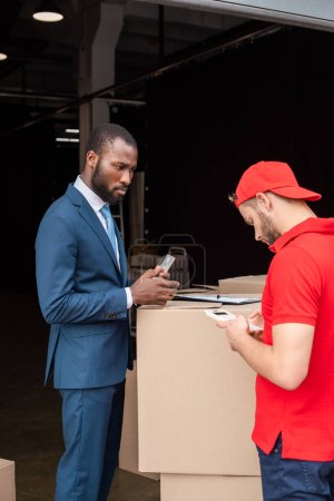african american client with money and caucasian delivery man with calculator