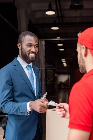 smiling african american client paying for delivery with cash