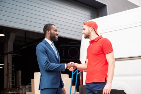 side view of multicultural client and delivery man shaking hands near van