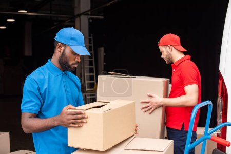 side view of multicultural delivery men in red and blue uniform with cardboard boxes