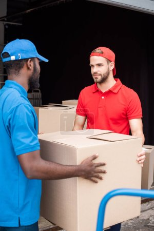 multicultural delivery men in red and blue uniform with cardboard boxes