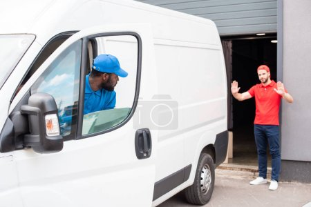 Photo for Multiethnic delivery men in uniform parking white van on street - Royalty Free Image