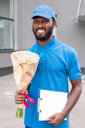 portrait of smiling african american delivery man with bouquet of flowers and cardboard in hands