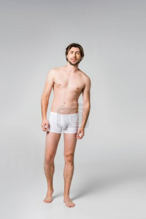 young man in white underwear posing on grey backdrop