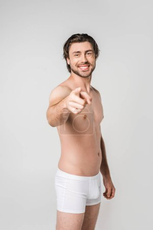 portrait of smiling man in white underwear pointing at camera isolated on grey