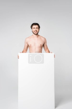 smiling shirtless man with blank banner on grey background