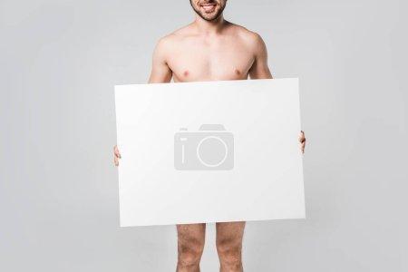 vue partielle d'un homme nu souriant tenant une bannière vierge isolée sur du gris