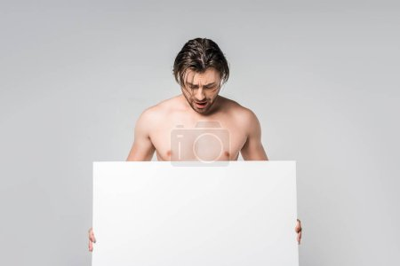 portrait of handsome shirtless man looking at blank banner in hands isolated on grey