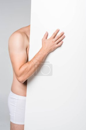 cropped shot of man with blank banner in underwear isolated on grey