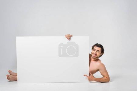 smiling handsome man pointing at blank banner on grey background