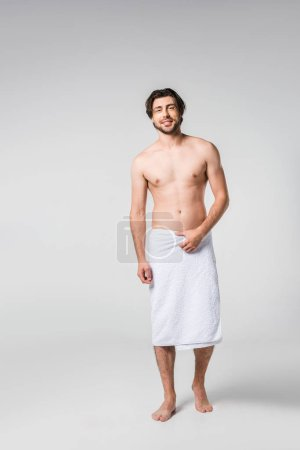 smiling handsome man in white towel on grey backdrop