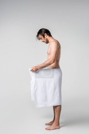 side view of handsome man in white towel looking down on grey background