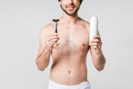partial view of smiling man in white towel with razor and shaving foam in hands isolated on grey