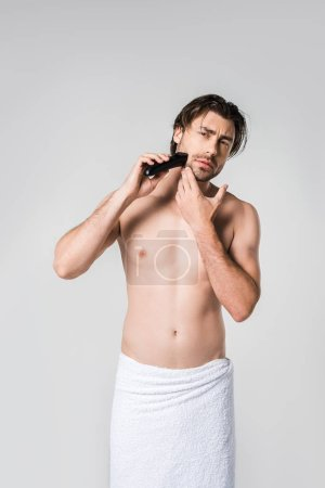portrait of man in white towel shaving beard with electric clipper isolated on grey