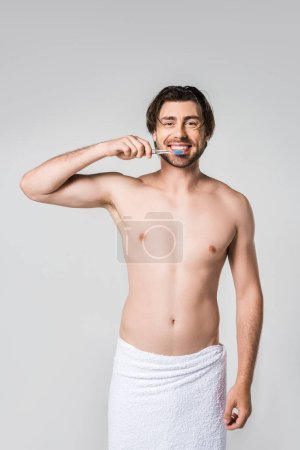 portrait of cheerful man in white towel with tooth brush isolated on grey