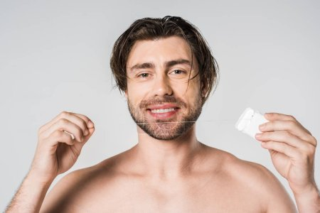 portrait of smiling man with dental floss isolated on grey