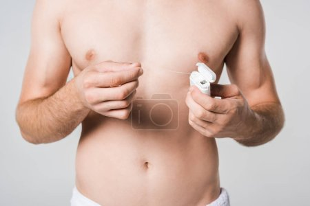partial view of shirtless man with dental floss isolated on grey