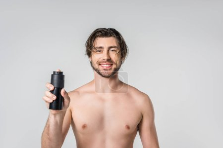 portrait of smiling shirtless man with male deodorant isolated on grey