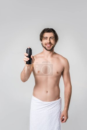 portrait of smiling handsome man in white towel with male deodorant isolated on grey